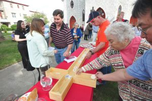"""""""Participants place spiritual offerings in a wooden cross during the first weekly Cathedral of the Night celebration on the lawn in front of St. Joseph's in Pittsfield on Sunday, September, 21, 2014. Gillian Jones / Berkshire Eagle Staff / photos.berkshireeagle.com"""""""